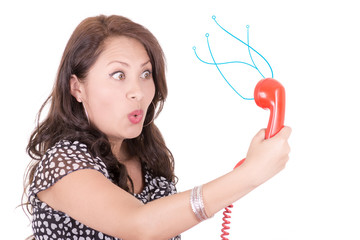 hispanic Woman looking into old telephone, communications