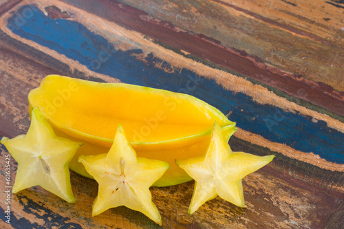 Carambola and slices on wooden table