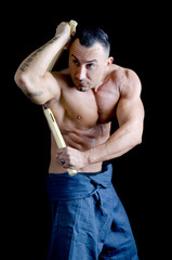 Muscular martial arts man shirtless using nunchuks
