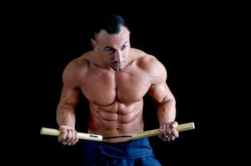 Muscular martial arts man shirtless using nunchuks