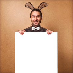 Fashion guy in  bunny with rabbit ears holding white board. Sale