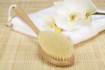 Handtuck, Badebürste und Orchidee auf Bambusmatte