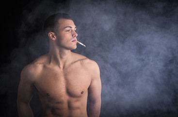 Muscular shirtless young man smoking sigarette