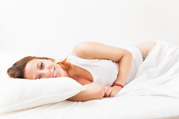 Long-haired woman lying on white sheet in bed at home