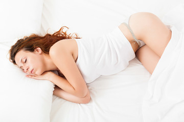 Pretty girl in white shirt sleeping on white pillow