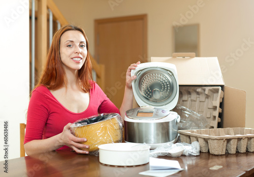 Cute red haired female with electric crock pot in her kitchen in