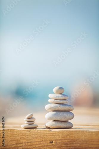 Juliste zen stones jy wooden banch on the beach near sea. Outdoor