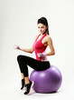 woman sitting on fitball with dumbells on gray background