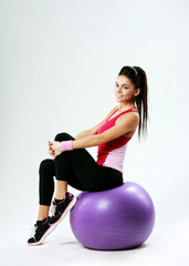 Young happy sport woman sitting on fitball on gray background