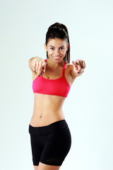 Young cheerful fit woman pointing at you on gray background