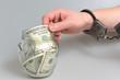 Постер, плакат: Рука в наручниках берет деньги из стеклянной банки