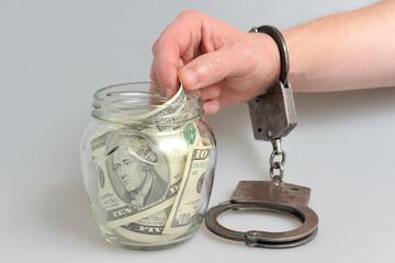 Рука в наручниках берет деньги из стеклянной банки