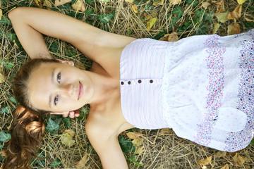 girl in a sundress lying on the grass