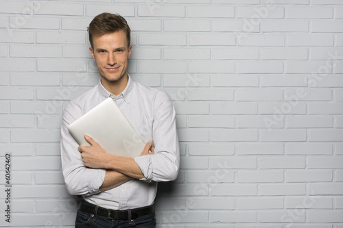 Handsome Cheerful man holding a laptop, isolated over a wall