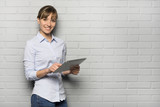 Pretty cheerful Woman holding a Tablet Pc, isolated over a wall