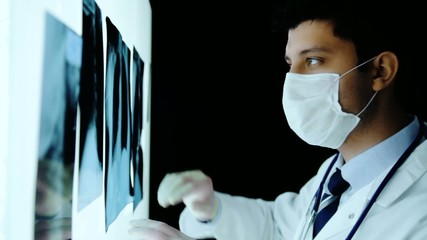 Handsome Young Surgeon Examining Scans Close Up