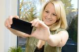 Frau fotografiert Selfie mit Smartphone poster