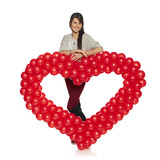 Smiling woman holding red balloon heart