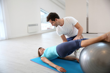 Woman doing pilates exercises with coach
