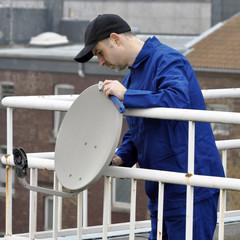 Techniker montiert Satelliten-Schüssel