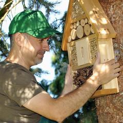 Gärtner montiert Insekten-Hotel