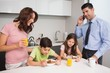 Kids with parents having breakfast in kitchen