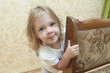 Девочка выглядывает из-за стула