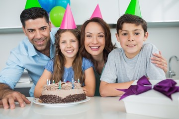 Family of four with cake and gifts at birthday party