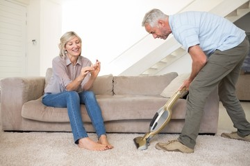 Woman filing nails while man vacuuming area rug