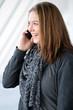 junge Frau mit Smartphone telefoniert ausgelassen