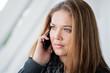 junge Frau mit Smartphone telefoniert nachdenklich