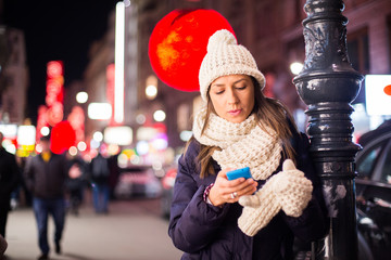 Young woman at night with mobile phone