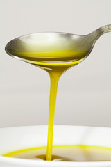 Olive oil falling down over a spoon