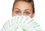 Close up of young happy woman holding pile of money