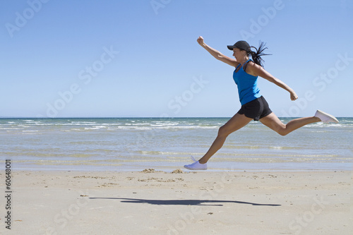 Fit woman leaping mid air on a beach