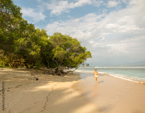 Young woman walking along tropical beach