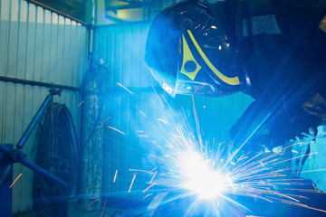 welder works with electric welding machine. metall