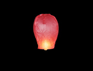 Single floating red sky lantern isolated on black