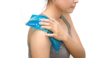 a woman applying cold pack on swollen hurting shoulder