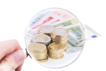 Euro Banknoten und Münzgeld unter eine Lupe