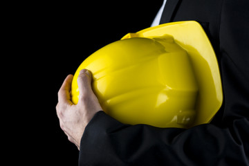 Man in a suit holding a yellow hardhat