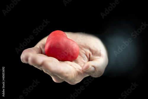 Man cupping a red heart in his hand