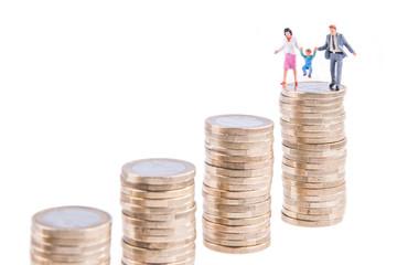 Familie mit Kind auf einem Stapel Euromünzen - Wachstum