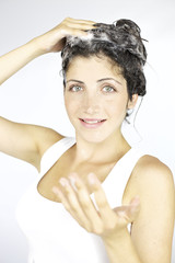 Smiling brunette with shampoo in hair
