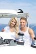 Junges Paar beim Segeln auf einer Yacht im Sommerurlaub