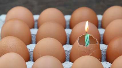 Raw break egg with happy birthday candle.