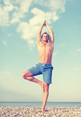 man doing yoga on the beach