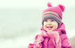 Happy baby girl in a pink hat and scarf