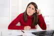 Gestresste junge Frau in Rot in der Arbeit oder beim Lernen