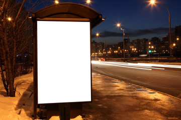Blank sign at bus stop in evening city